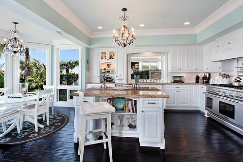 this glamorous coastal white kitchen speaks for itself the sky blue tray ceiling paired with the huge bank of floor to ceiling windows evokes the feeling